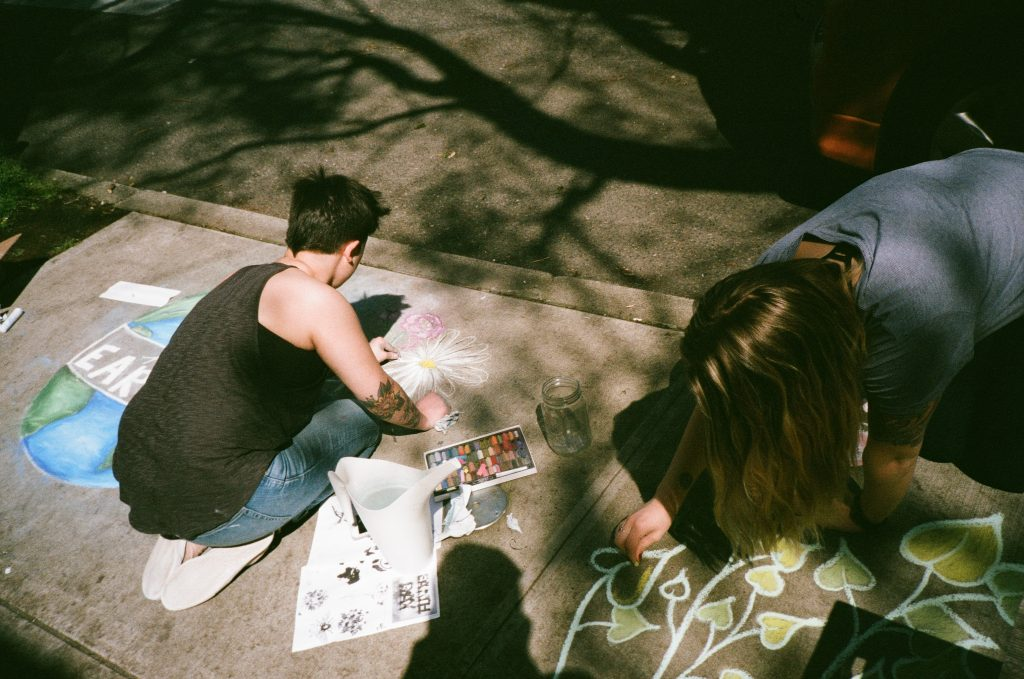 Two people drawing chalk artwork on the sidewalk